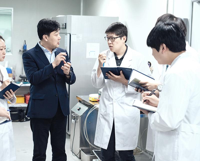실험실에서 토론을 하고 있는 교수와 학생들 이미지