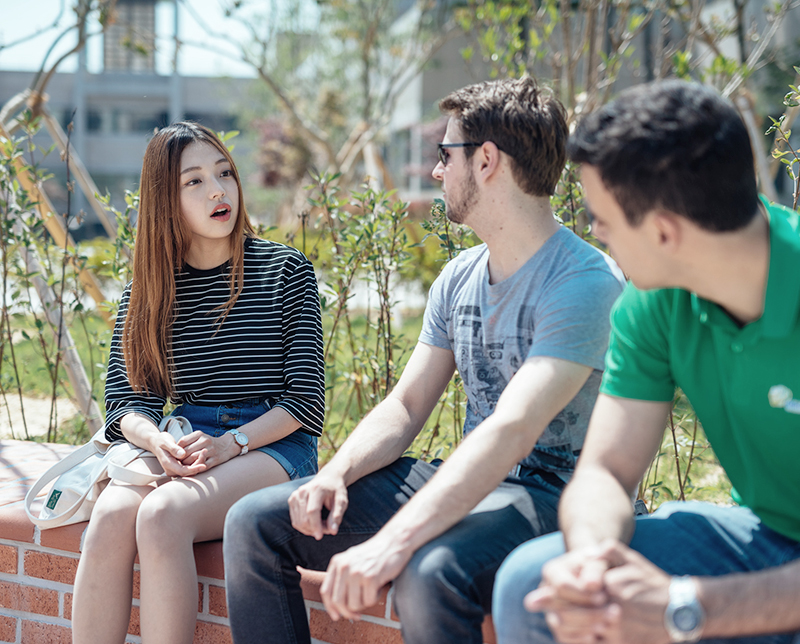 화단에서 대화를 나누는 학생들 이미지