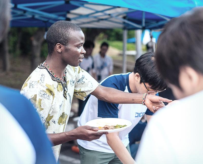 학생들이 봉사활동을 하면서 음식을 나워주는 이미지